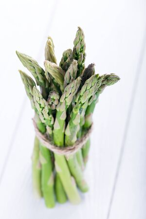 Fresh green asparagus on white wooden board, macro and shallow depth Stock Photo