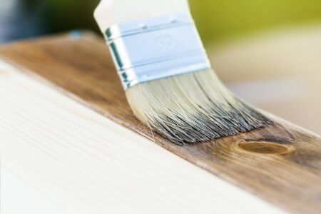 Applying wood stain on wooden board, painting process of repair, macro shot. Stock Photo