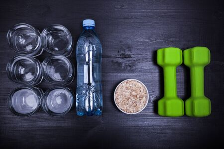 Concept plan for drinking pure water for healthy lifestyle and weightloss, fitness and diet food for workout, top view and selective focus on black wooden background, nobody