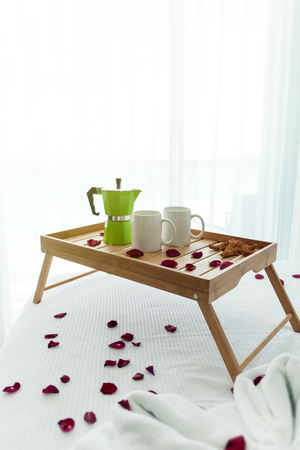 Breakfast wooden tray with coffee percolator and cups, decorated red rose petals on bed, window view background, romantic concept, nobody