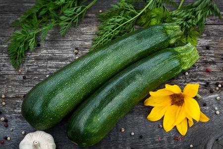 cucurbit: Fresh organic zuchini with sunflower on old wood Stock Photo