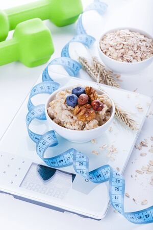 vitamine: Electronic digital kitchen scale with oatmeal, measuring tape and green dumbbells on background