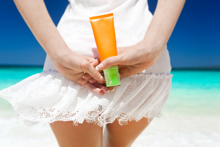 suncare: Portrait of woman holding sunscreen cream on beach, back view, beauty care concept Stock Photo