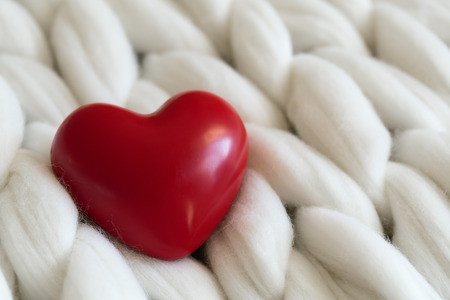 st  valentine: St. Valentine concept decoration card. Red heart shape on woolie knitted background, shallow depth