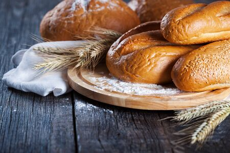 Fresh bakery goods. Different types of bread with sheaves of golden wheat on rustic wooden board.