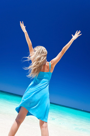 Happy blond girl on beach with outstretched arms, feeling freedom, back view. Vacation concept