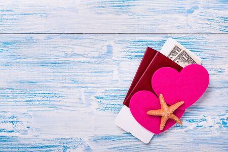 Luna di miele tropicale Passaporti con carta d'imbarco, banconote in dollari e forme di cuore su fondo di legno rustico blu