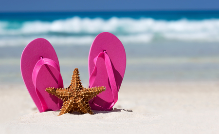 Pink flip flops and starfish on white sandy beach. Summer vacation concept