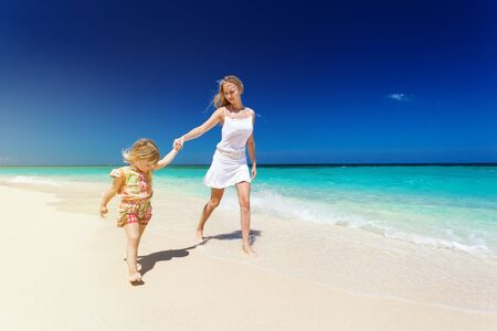 Mother and daughter having fun on white sandy beach, enjoying tropical nature and summer vacation photo