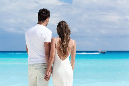 Newlyweds in love on beach looking to the sea and holding their hands Stock Photo