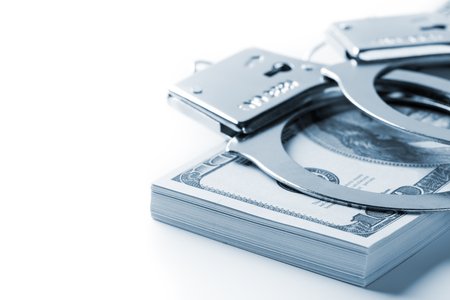 Pair of handcuffs closeup on dollar and euro banknotes stacks. Corruption problem in the world. Blue tone