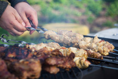 shallow dof: Cooking lamb steaks and pork kebab on grill, skewered pork meat in hand, outdoor. Selective focus and shallow DOF Stock Photo