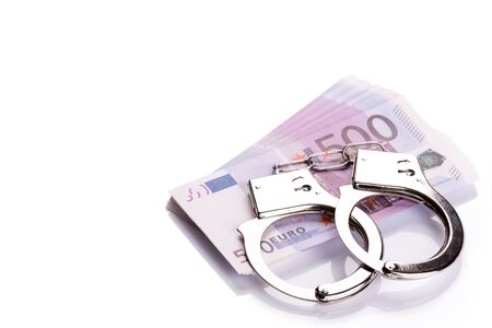 jail: Pair of handcuffs closeup on euro banknotes stack. Corruption problem in the world