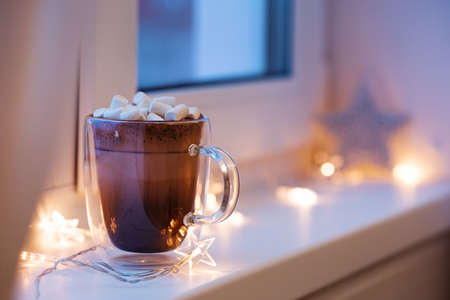 resistant: Hot cocoa in cup with mini marshmallows on window sill, decorated lights garland, sweet chocolate beverage in double wall glass mug, cozy morning, nobody. Shallow depth and toned image Stock Photo