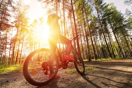 spokes: Woman riding a mountain bicycle along path at the forest. Healthy lifestyle and sport concept