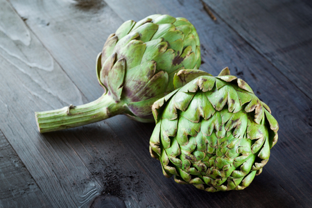 Fresh green artichokes on wooden board