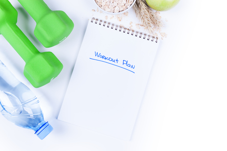 Personal workout plan with bottle of water, dumbbells and fitness food, oatmeal and fruits on white, top view. Healthy lifestyle concept frame with copyspace. Stock Photo