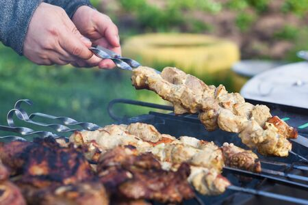 Cooking lamb steaks and pork kebab on grill, skewered pork meat in hand, outdoor. Selective focus and shallow DOF Stock Photo