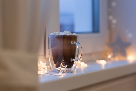 resistant: Hot cocoa in cup with mini marshmallows on window sill, decorated lights garland, sweet chocolate beverage in double wall glass mug, cozy morning, nobody. Shallow depth