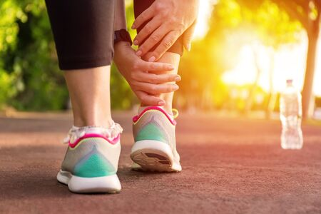 Female athlete runner touching foot in pain,closeup, fitness woman running in summer park. Healthy lifestyle and sport concept