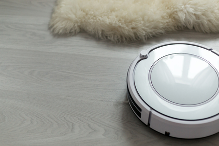 living room interior: White robotic vacuum cleaner on laminate floor cleaning dust in living room interior. Smart electronic housekeeping technology