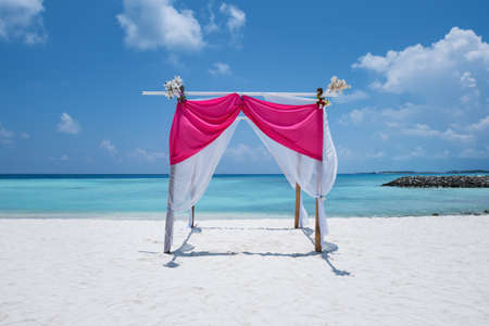 Wedding arch decorated with flowers and soft cloth.  Marriage on tropical beach