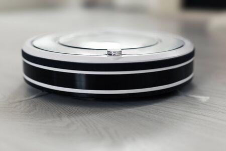 積層の床のリビング ルームのインテリアのほこりをクリーニングで白いロボット掃除機。スマート電子清掃技術