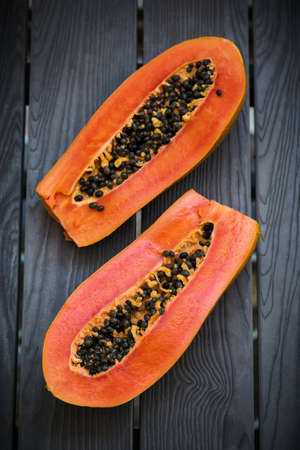 Slices of fresh cutted papaya on dark board, healthy detox concept, top view