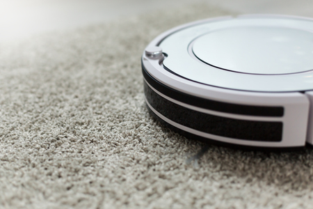 dirty room: White robotic vacuum cleaner on laminate floor cleaning dust in living room interior. Smart electronic housekeeping technology