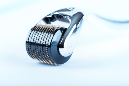 Derma Roller on white, microneedle mesotherapy for skincare, rejuvenating treatment concept.