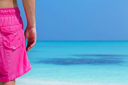Back view of a man in bright colour pink beach cloth, looking to sea and enjoying summer vacations. Concept travel card with copy space for your text Stock Photo