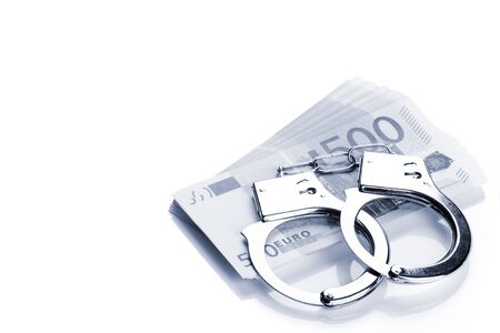 Pair of handcuffs closeup on euro banknotes stack. Corruption problem in the world. Blue tone Stock Photo