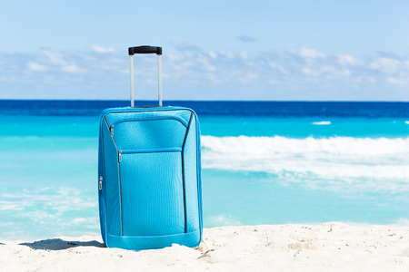 Color travel suitcase on sandy beach with turquoise sea background, summer holidays concept Stock Photo