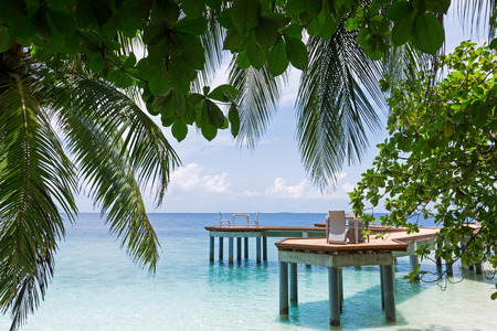 Wooden pier on maldivian island with crystal water, travel vacation