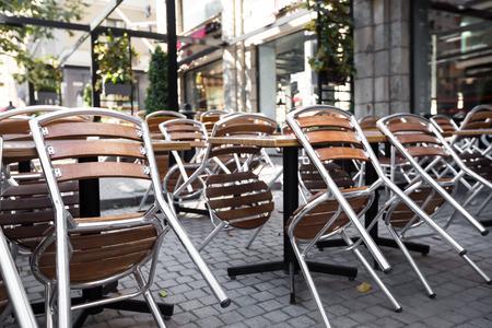 Café fermé à l'extérieur avec des chaises renversées sur les tables, personne Banque d'images