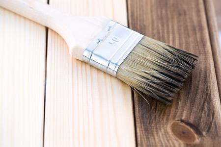 Applying wood stain on wooden board, painting process of repair, macro shot. 免版税图像