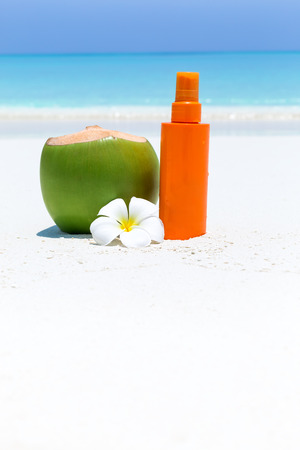 Skin care on summer vacations. Tube with sun screen SPF protection on tropical sea shore decorated plumeria. Copy space for your text Stock Photo