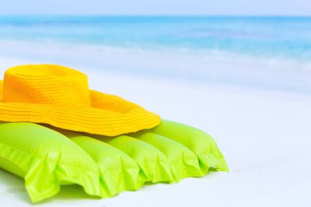 Inflatable air swim mattress and summer hat on sandy coastline close to turquoise sea, beach summer accessories.  Stock Photo