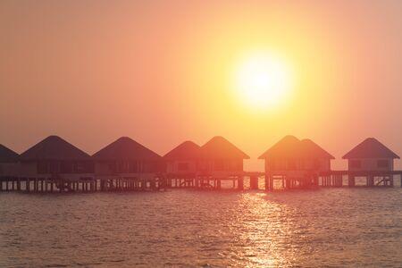 Sunset scene at Maldives beach, luxury water lodges 스톡 콘텐츠