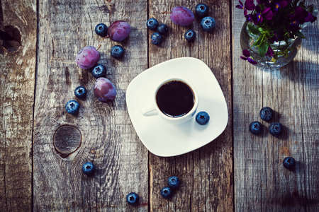 A cup of morning coffee decorated purple berries on old wooden background