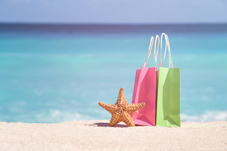 Shopping bags and starfish on sand against turquoise caribbean sea water. Tropical celebration on beach