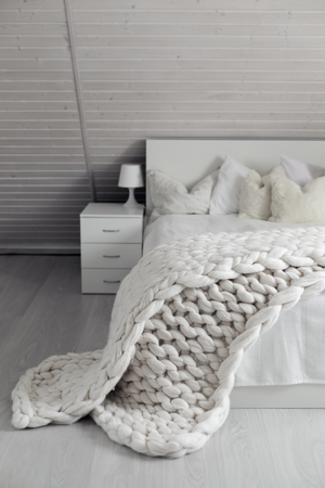 Cozy white scandinavian bedroom interior at loft.  Beautiful merino woolen plaid decorated bed and floor, super chunky yarn knitted blanket, nobody