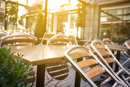 Closed outdoors cafe with overturned chairs on tables, Nobody