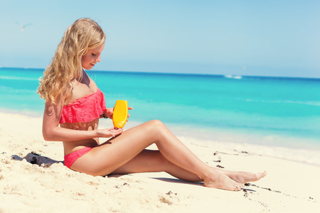 Tanning blond woman on summer vacation sitting on white sandy beach and applying sunscreen body care lotion, closeup to sea Stock Photo