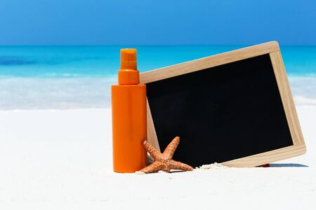 Sunscreen lotion in orange tube with chalk board decorated star fish on sandy beach. Skin care concept card with sea background. Stock Photo