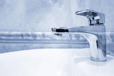 Modern metal faucet in bathroom, closeup. Blue tone  Stock Photo