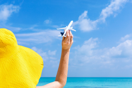 Model airplane in female hand on turquoise sea background. Woman in yellow summer hat holding miniature aircraft, travel vacation card Stockfoto