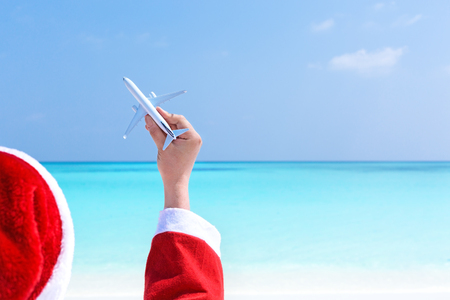 Santa Claus relaxing at chaise longue and holding airplane model in hand on sea background with copy space. Concept of celebration Christmas on beach and enjoy winter holidays at tropical destination