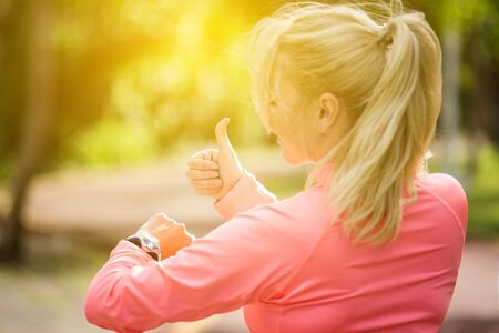 Sports athlete runner woman looking at heart rate monitor after jogging. Healthy lifestyle and sport concept   Stock Photo