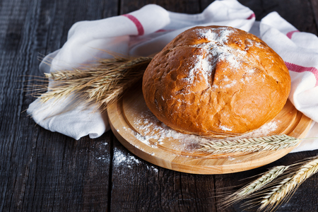 Round freshly bared homemade bread on board with ears of barley on rustic wooden background